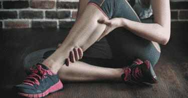 Mulher sentada sentindo caibra na perna