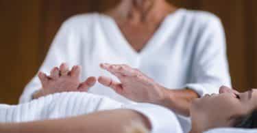 Terapeuta aplica reiki em mulher deitada.