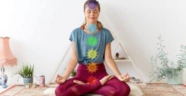 Mulher sentada no chão, meditando, com ilustrações de chackras sobre seu corpo.