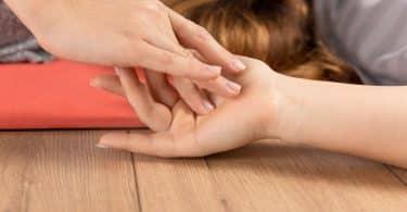Pessoa encostando na mão de outra pessoa que está no chão