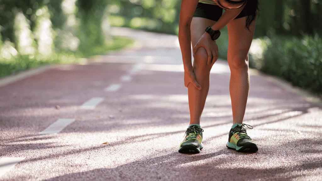 Mulher sentindo cãibra na perna durante corrida.