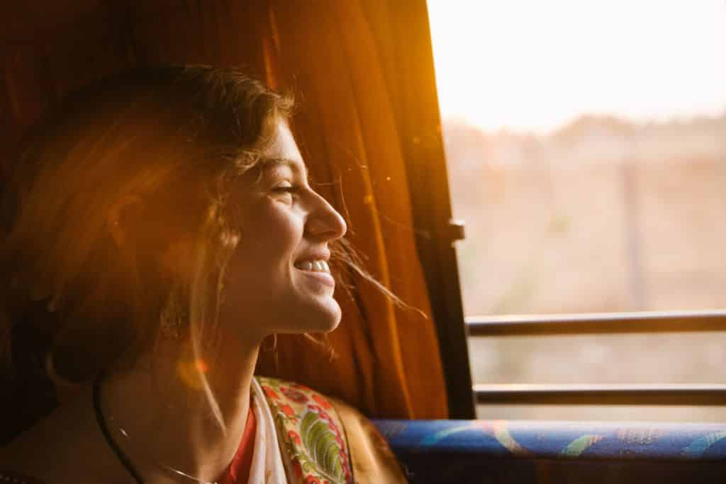 Mulher sorrindo de olhos fechados com o reflexo do sol em seu rosto