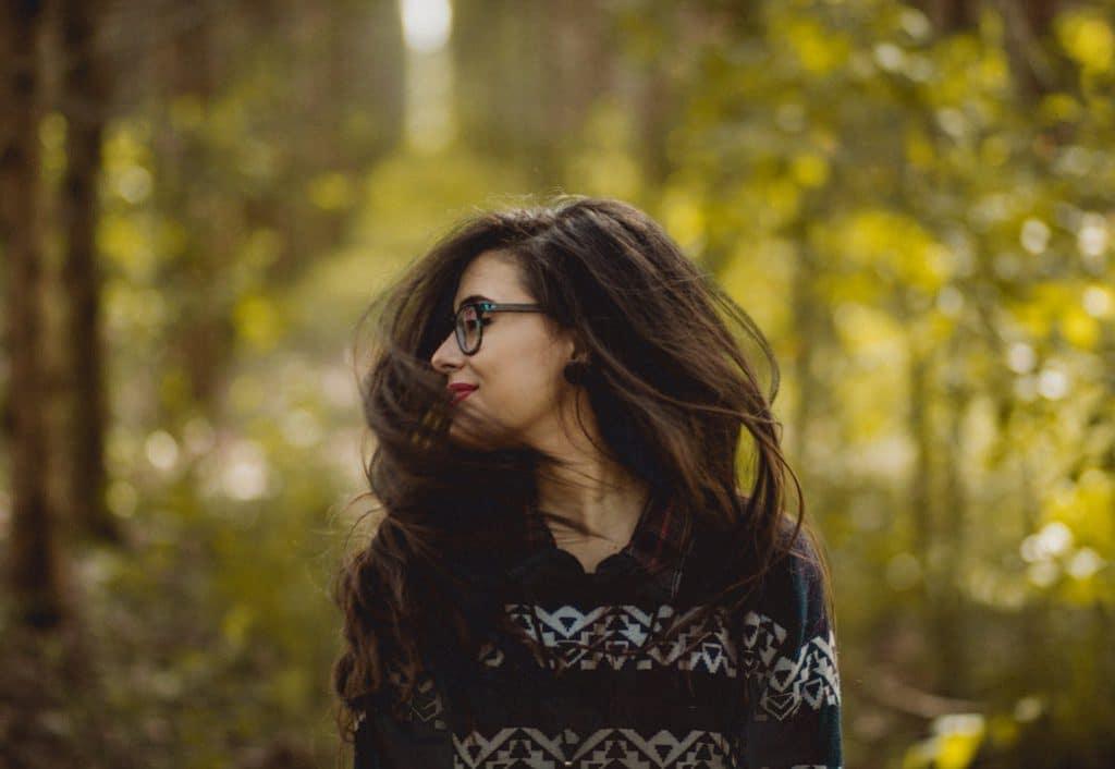 Mulher em uma floresta. A foto está pegando o movimento em que ela está mexendo a cabeça.
