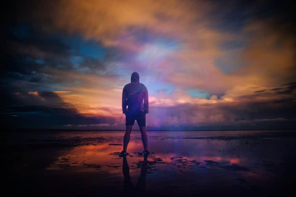 Homem em uma praia olhando para o horizonte.