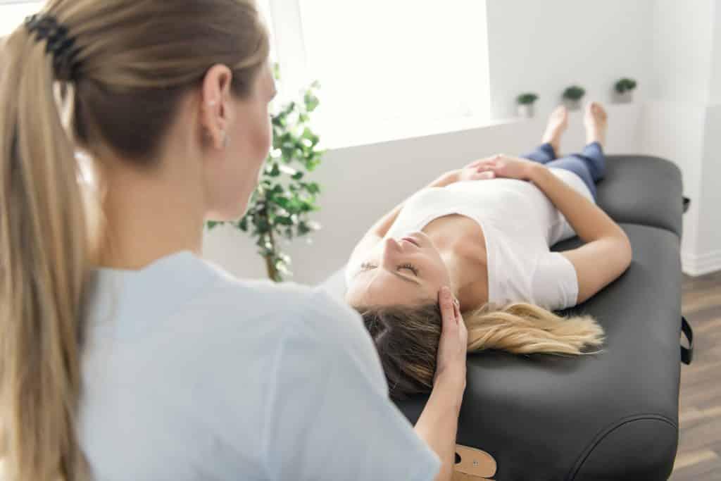 Médica com as mãos no rosto da paciente deitada