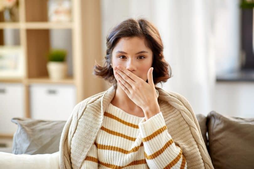 Mulher sentada no sofá com a mão em sua boca