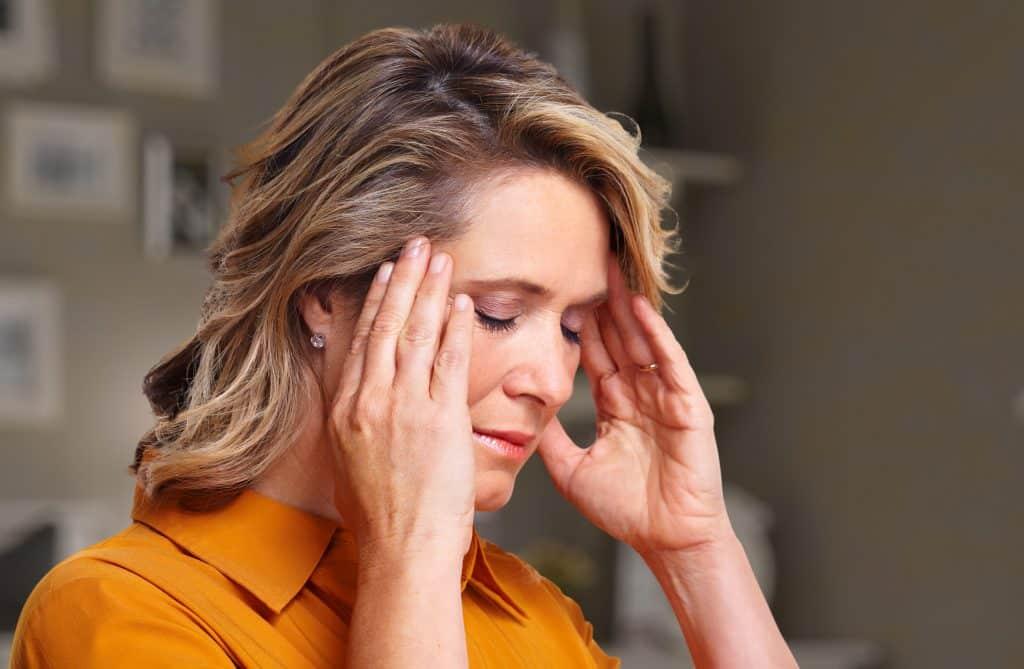 Mulher com as mãos na cabeça sentindo dor