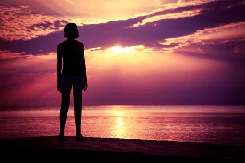 Silhueta de uma mulher assistindo ao pôr do sol.