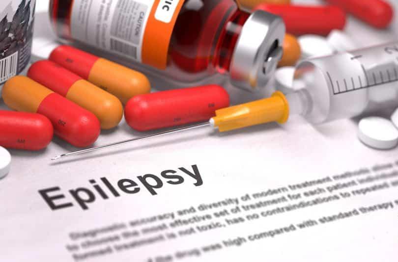"""Folha de papel escrito """"Epilepsia"""" ao lado de remédios"""