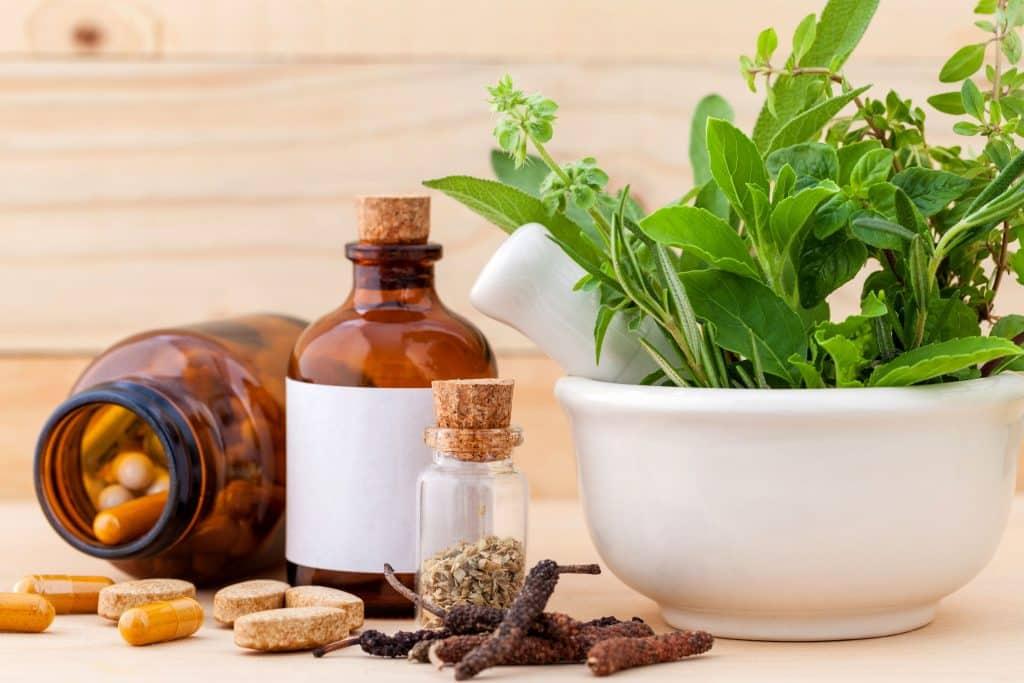 Potinhos com remédios e um recipiente com folhas