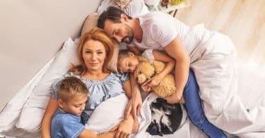 Mãe, pai, seus dois filhos e seu gato dormindo na mesma cama, vistos de cima.