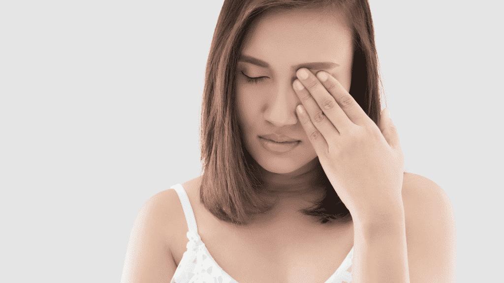 Mulher cobrindo o olho esquerdo com conjuntivite