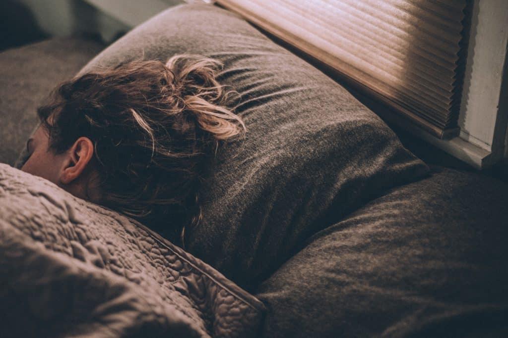 Mulher deitada na cama dormindo
