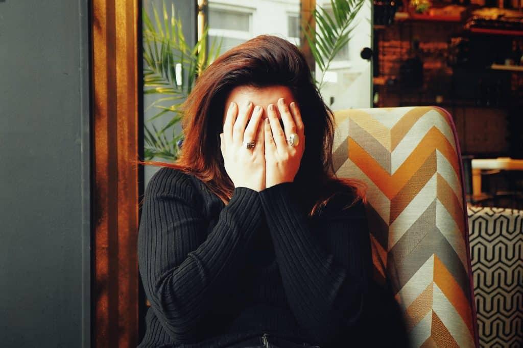 Mulher sentada em um sofá com as mãos cobrindo o rosto