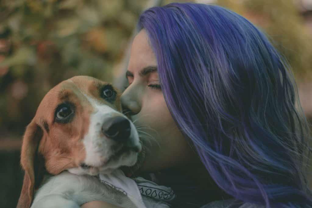 Mulher beijando rostinho do cão