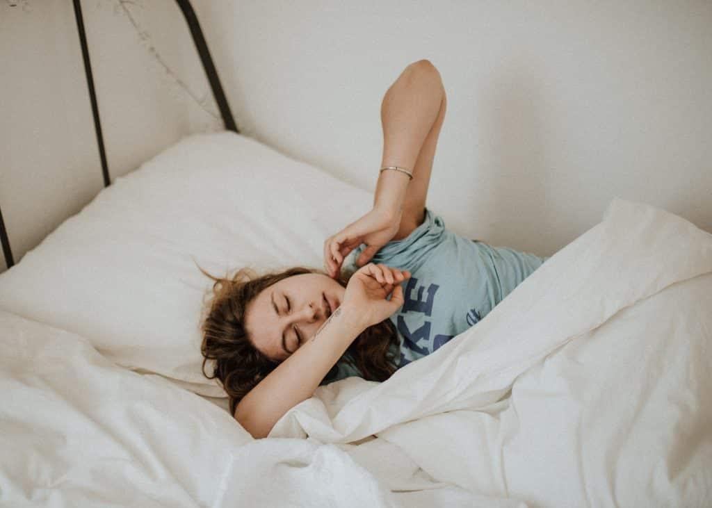 Mulher deitada na cama com os olhos fechados com seus braços apoiados no rosto