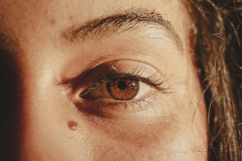 Recorte de um rosto de uma mulher com o olho cor de mel.