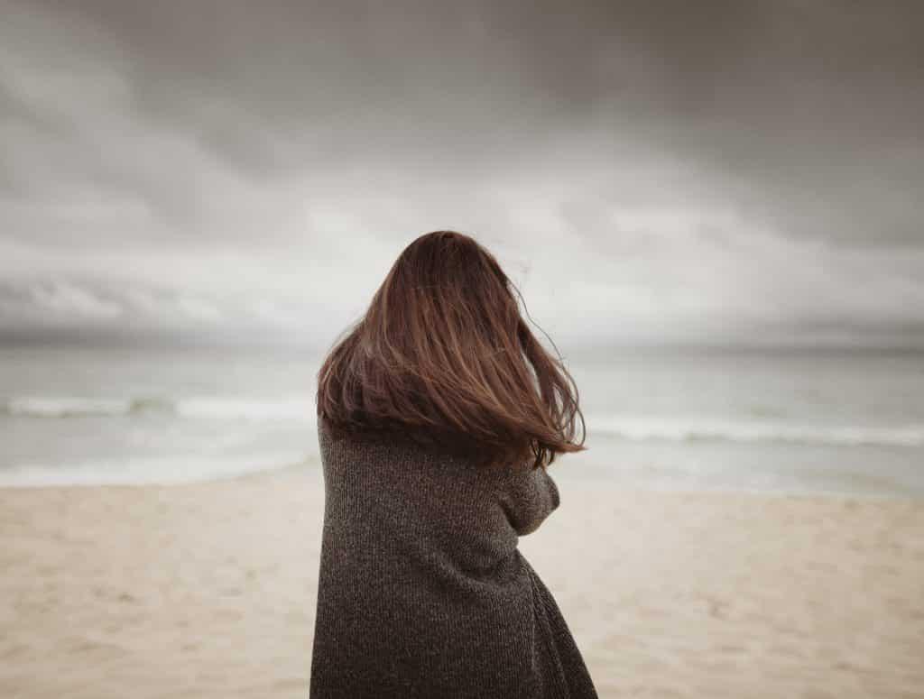Mulher olhando para o mar da praia