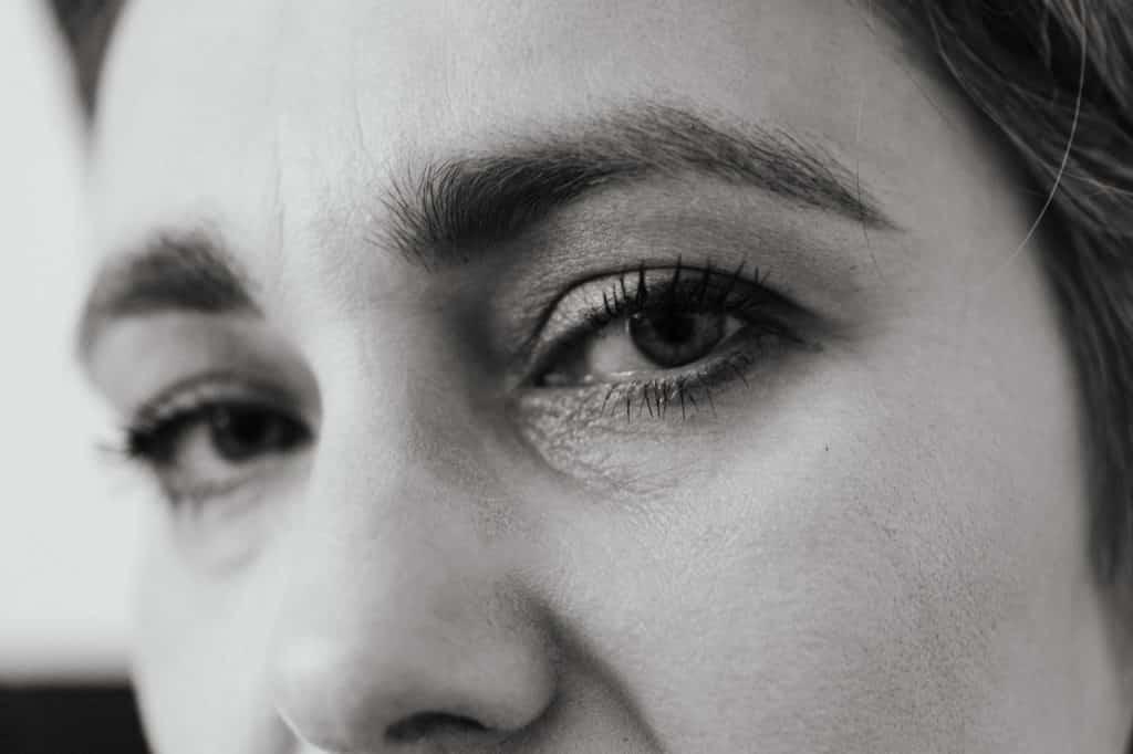 Close do rosto de uma mulher em uma imagem preto e branco.