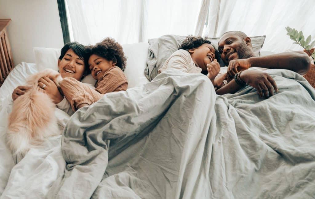 Família de pai, mãe, seus dois filhos e seu gato de estimação deitados em uma cama, juntos.