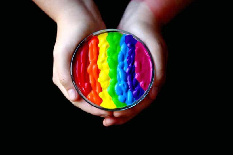 Mãos de alguém segurando portinho com tintas coloridas