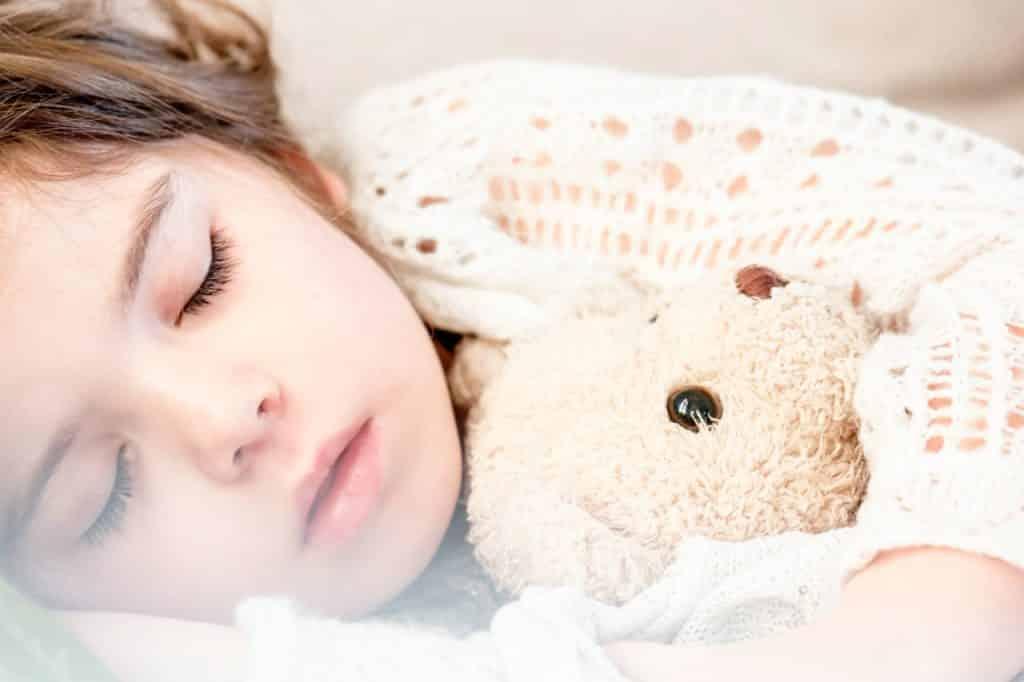 Criança dormindo, vista de perto, deitada enquanto segura seu urso de pelúcia.