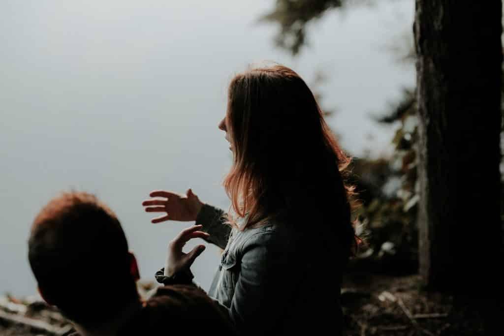 Mulher falando com pessoa ao seu lado e gesticulando com as mãos