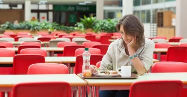 Mulher triste sentada em refeitório vazio, em frente a uma bandeja com comida intocada.