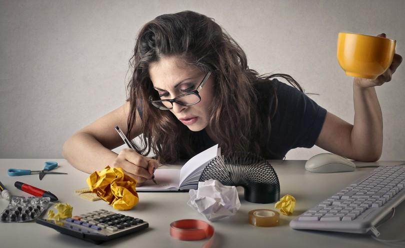 Mulher escrevendo em seu caderno na mesa de escritório