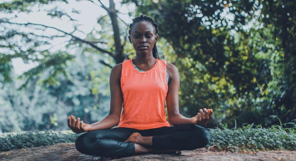 Mulher sentada no chão de um parque natural, meditando ao ar livre.