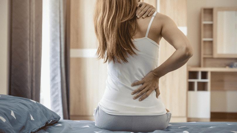 Mulher com dor na lombar sentada na cama