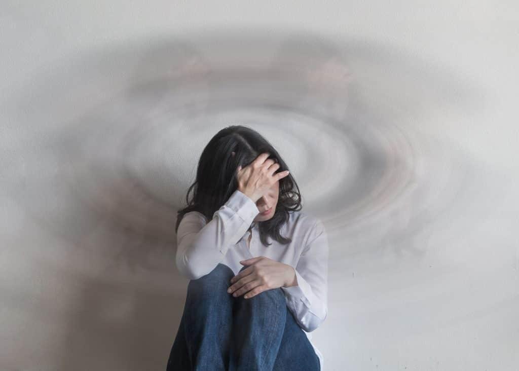 Mulher sentada no chão com a mão na cabeça