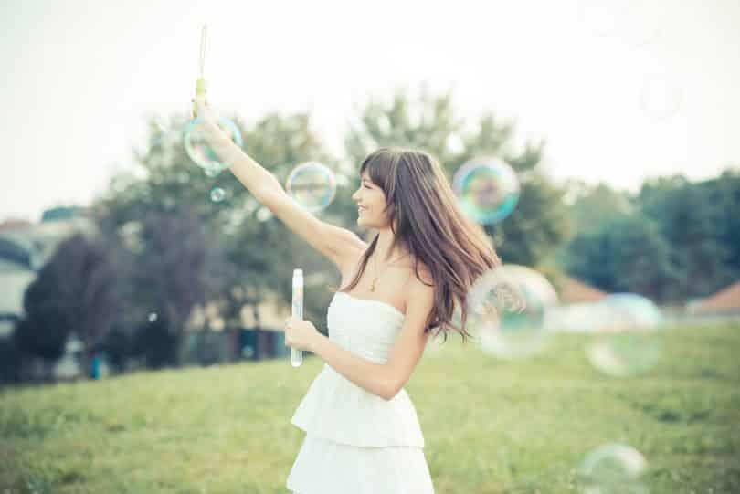 Mulher jovem sorrindo e brincando com bolhas de sabaão em um parque.