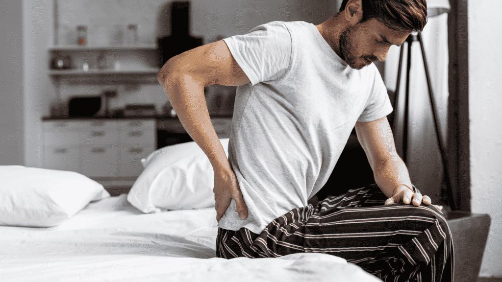 Homem se levantando da cama sentindo dor na lombar