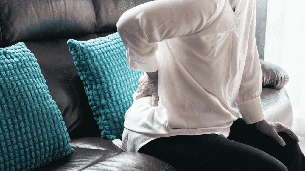 Mulher idosa sentada no sofá com dor na coluna