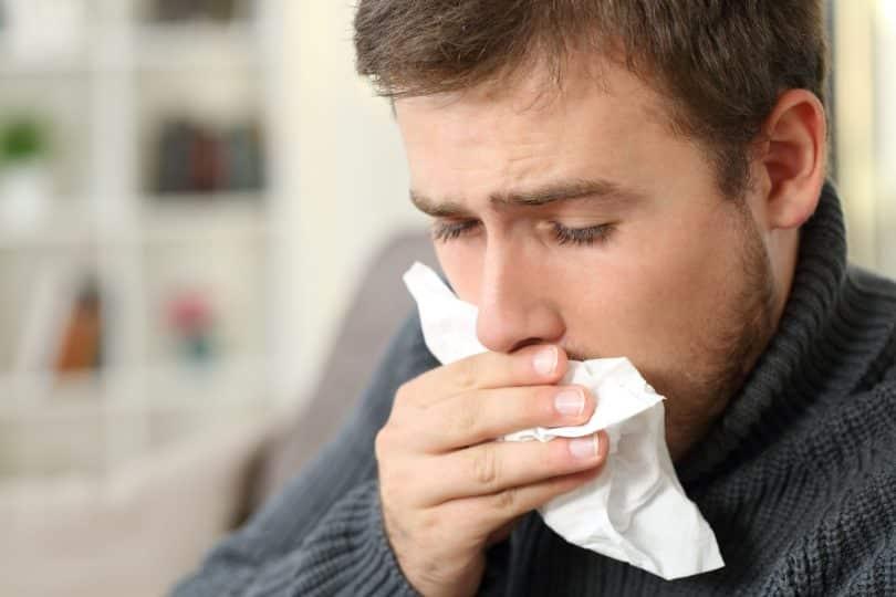 Homem tossindo, cobrindo a boca com um lenço de papel, sentado em um sofá no interior de uma casa.