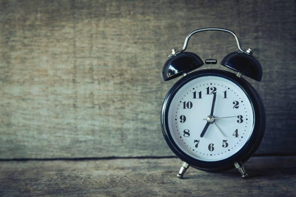 Relógio com alarme e os ponteiros indicando alguns minutos depois das sete horas.