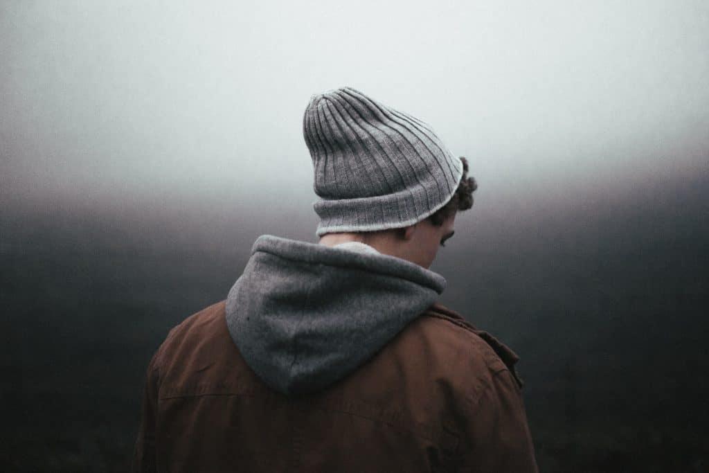 Homem pensativo olhando para o lado em um fundo cinza