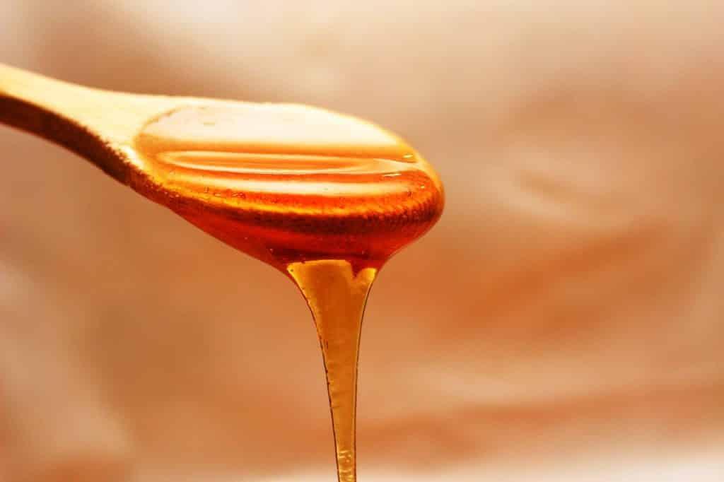 Colher de madeira cheia de mel, a ponto de escorrer na ponta.
