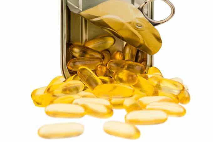 Lata de sardinha aberta e inclinada, com capsulas em gel de um líquido amarelo saindo do interior.