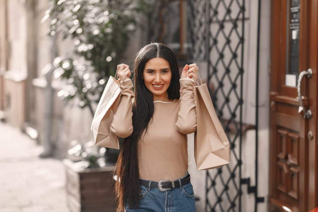 Mulher sorrindo e segurando sacolas de papel, indicando compras.
