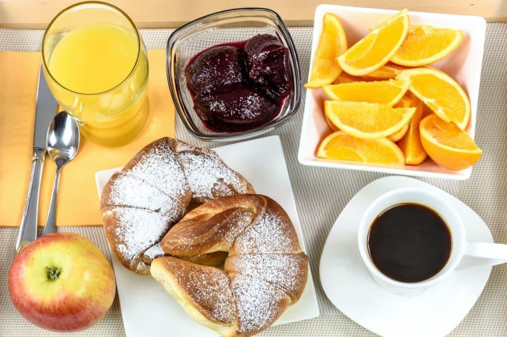 Mesa com pedaços de laranja, uma maçã, uma xícara de café, um copo de suco, e uma tigela com açaí.