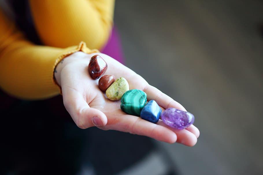 Mão estendida com 6 pequenos cristais coloridos representando os chakras.