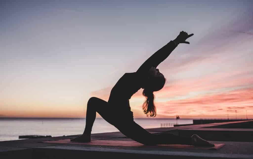 Mulher praticando Yoga de frente para o mar