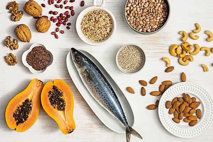 Alimentos ricos em magnésio como mamão, peixe e castanhas, sobre uma mesa.