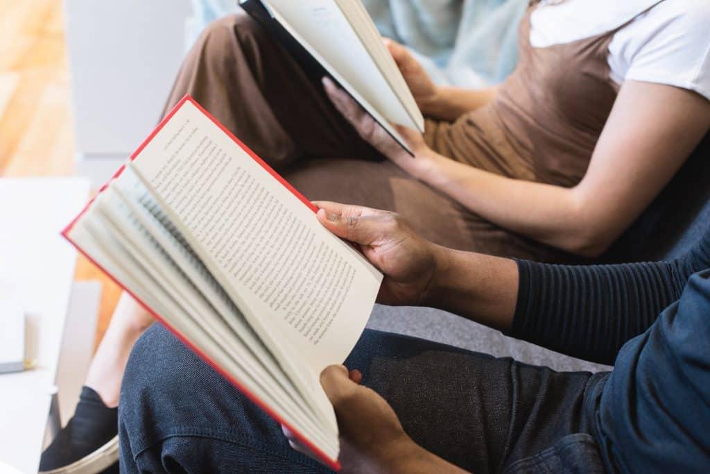 Três pessoas sentadas lado a lado lendo livros em uma sala de espera.