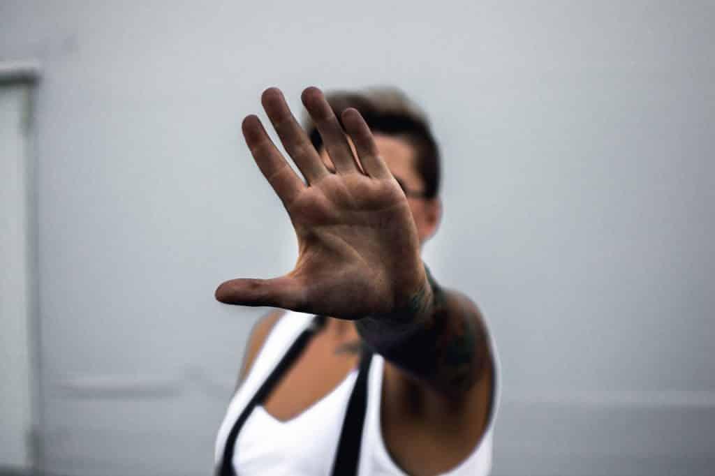 Pessoa com o braço esticado, e a mão aberta, mostrando sua palma, indicando um pedido para parar.
