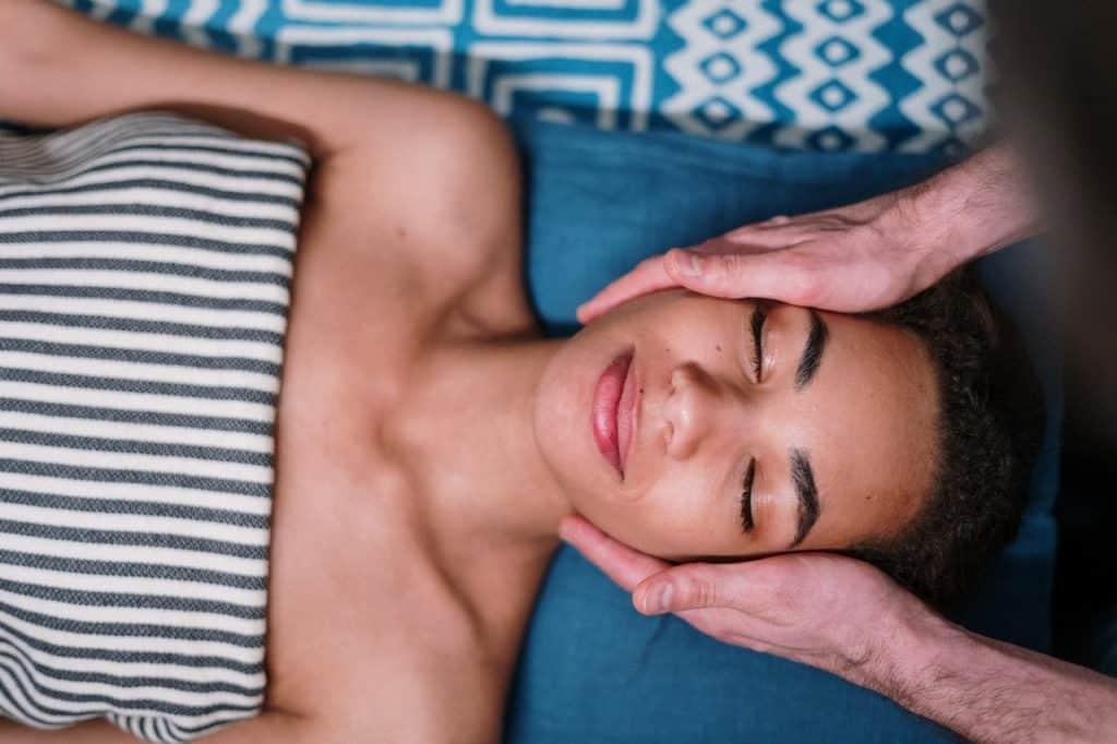 Mulher deitada com os olhos fechados enquanto recebe massagem facial.