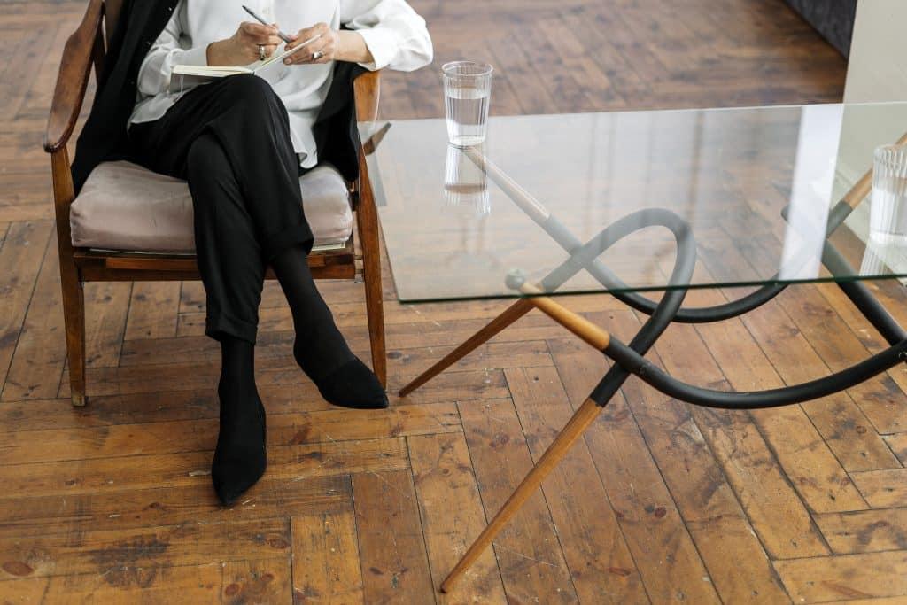 Psicóloga segurando caderno e caneta em frente a mesa