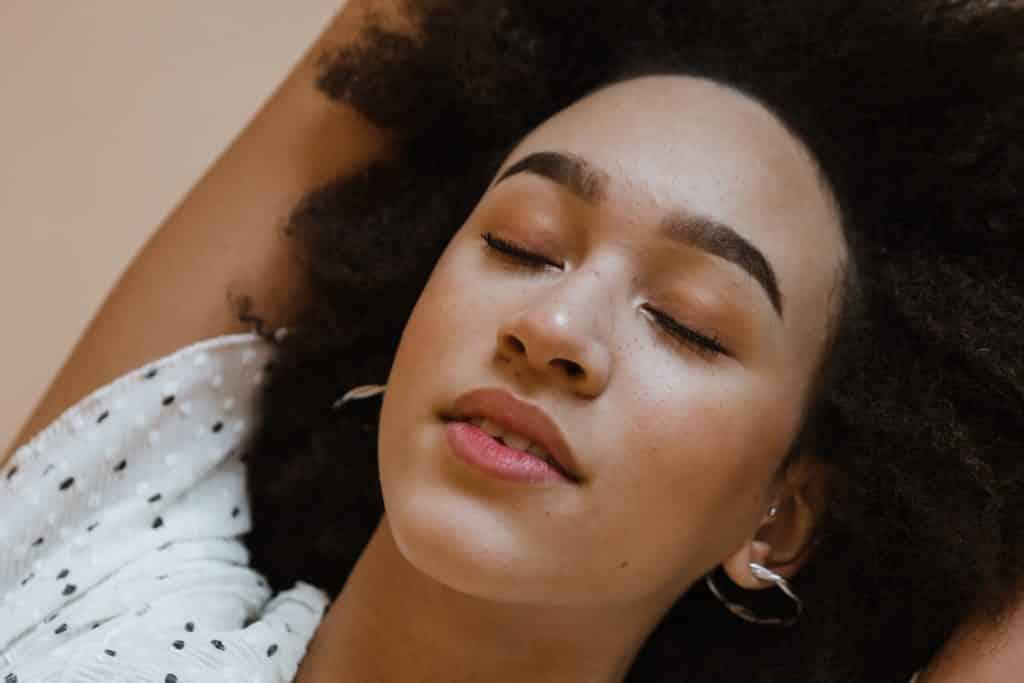 Mulher deitada de olhos fechados